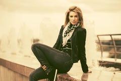 Счастливая молодая женщина моды в кожаной куртке на открытом воздухе стоковое изображение