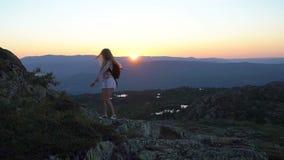 Счастливая молодая женщина на заходе солнца высоком в горах с открытыми развевая руками видеоматериал
