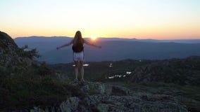 Счастливая молодая женщина на заходе солнца высоком в горах с открытыми развевая руками сток-видео