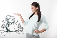 Счастливая молодая женщина показывая снеговик после делать его с детьми Стоковое Изображение