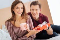 Счастливая молодая женщина получая подарок от парня Стоковая Фотография