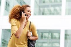 Счастливая молодая женщина разговаривая с мобильным телефоном в городе стоковые фотографии rf