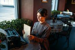Счастливая молодая женщина сидит таблицей в кафе Стоковое Изображение RF
