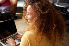 Счастливая молодая женщина сидя в деятельности кафа с ноутбуком стоковые изображения