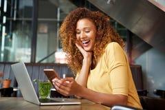 Счастливая молодая женщина сидя в кафе с ноутбуком и мобильным телефоном стоковое изображение