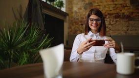 Счастливая молодая женщина сидя в кофейне отправляя СМС на ее умном телефоне видеоматериал