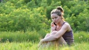 Счастливая молодая женщина сидя на зеленой лужайке и говоря на телефоне или smartphone видеоматериал