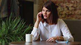 Счастливая молодая женщина сидя на софе в уютной одежде с чашкой кофе сток-видео