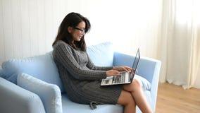 Счастливая молодая женщина сидя на софе и используемой компьтер-книжке дома видеоматериал