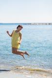 Счастливая молодая женщина скача на пляж моря стоковая фотография rf