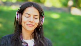 Счастливая молодая женщина смешанной гонки слушая музыку на наушниках Испанские танцы девушки хипстера к ритму и петь вперед видеоматериал