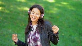 Счастливая молодая женщина смешанной гонки слушая музыку на наушниках Испанские танцы девушки хипстера к ритму и петь вперед акции видеоматериалы