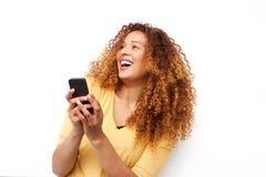 Счастливая молодая женщина смеясь с мобильным телефоном против белой предпосылки стоковая фотография rf