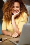 Счастливая молодая женщина смотря ноутбук стоковые изображения