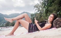 Счастливая молодая женщина со смартфоном ослабляя на тропическом пляже стоковое изображение