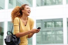 Счастливая молодая женщина с в городом с мобильным телефоном стоковые изображения