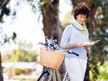 Счастливая молодая женщина с книгой чтения велосипеда стоковые фото