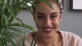 Счастливая молодая женщина с красивыми глазами усмехаясь через листья завода в комнате акции видеоматериалы