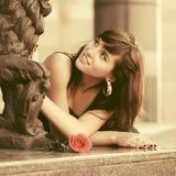Счастливая молодая женщина с красной розой в улице города стоковые изображения