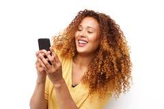 Счастливая молодая женщина с мобильным телефоном удерживания вьющиеся волосы белой предпосылкой стоковое фото