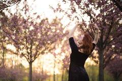 Счастливая молодая женщина танцора перемещения наслаждаясь свободным временем в парке вишневого цвета Сакуры - кавказская белая д стоковая фотография rf
