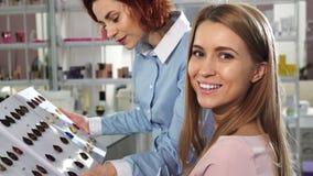 Счастливая молодая женщина усмехаясь к камере выбирая цвет краски волос с ее парикмахером стоковое изображение