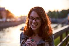 Счастливая молодая женщина усмехаясь с зубами усмехается outdoors и идущ на улицу города на одеждах зимы времени захода солнца we стоковое изображение