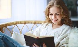 Счастливая молодая женщина читая книгу окном стоковые изображения