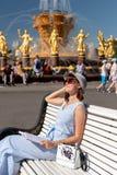 Счастливая молодая и стильная женщина со шляпой и книгой сидя на стенде в парке стоковая фотография rf
