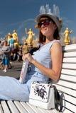 Счастливая молодая и стильная женщина со шляпой и книгой сидя на стенде в парке стоковые изображения rf