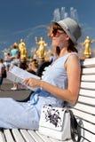 Счастливая молодая и стильная женщина со шляпой и книгой сидя на стенде в парке стоковое изображение