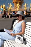 Счастливая молодая и стильная женщина со шляпой и книгой сидя на стенде в парке стоковые фото