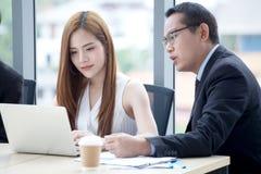 счастливая молодая команда бизнесмена и коммерсантки работая вместе с ноутбуком на столе обсуждая информацию в офисе Босс стоковое изображение rf