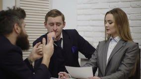 Счастливая молодая команда бизнесмена и коммерсантки работая вместе с бумажными docs на столе обсуждая информацию в офисе акции видеоматериалы