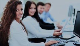 Счастливая молодая коммерсантка смотря задними и ее коллеги работают Стоковое фото RF