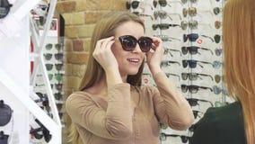Счастливая молодая красивая женщина пробуя на солнечных очках на магазине оптики видеоматериал