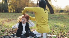 Счастливая молодая мать и ее маленькая дочь redhead имея потеху в парке осени Они играя и смеясь над движение медленное видеоматериал