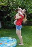 Счастливая молодая мать принимая ее сына младенца из раздувного бассейна стоковое изображение
