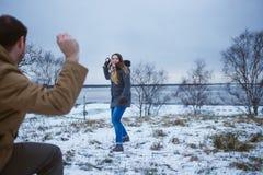 Счастливая молодая пара в зиме одевает играть снежные комья outdoors Стоковая Фотография RF
