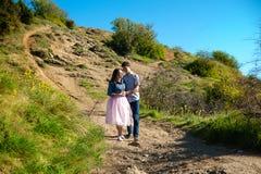 Счастливая молодая пара в обнимать влюбленности наслаждается весенним днем, любящий человек держа дальше вручает его женщину бесп стоковая фотография rf