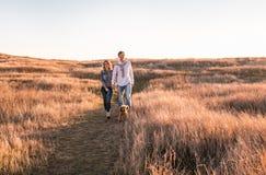Счастливая молодая пара идет с собакой стоковая фотография rf