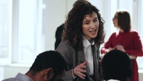 Счастливая молодая привлекательная кавказская бизнес-леди главного исполнительного директора говоря с африканскими мужскими работ сток-видео