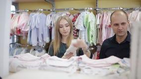 Счастливая молодая семья выбирает одежды для их нерождённого ребенка Беременная женщина в магазине Магазин товаров ` s детей видеоматериал