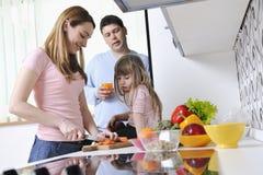 Счастливая молодая семья в кухне Стоковая Фотография RF
