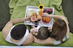 Счастливая молодая семья ест завтрак в кровати Стоковая Фотография RF