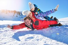 Счастливая молодая семья играя в свежем снеге на красивом солнечном зимнем дне внешнем в природе стоковые фотографии rf