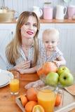 Счастливая молодая семья имеет время обеда с свежей едой фруктов и овощей в яркой кухне Смешная девушка с мамой дальше стоковые фото