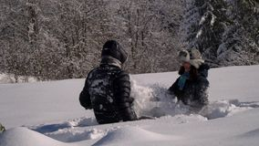 Счастливая молодая семья имеет потеху играя в снеге Они бросают снег и смех Они также весело падают в снег сток-видео