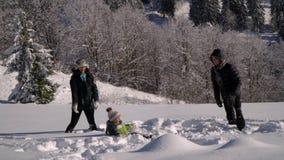 Счастливая молодая семья имеет потеху играя в снеге Они бросают снег и смех Они также весело падают в снег видеоматериал
