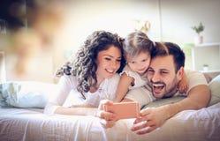 Счастливая молодая семья принимает автопортрет с умным телефоном стоковая фотография